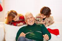 Lachender Opa mit Enkeln zu Weihnachten