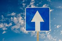Blue arrow directional road sign outdoors on the day blue sky with clouds background
