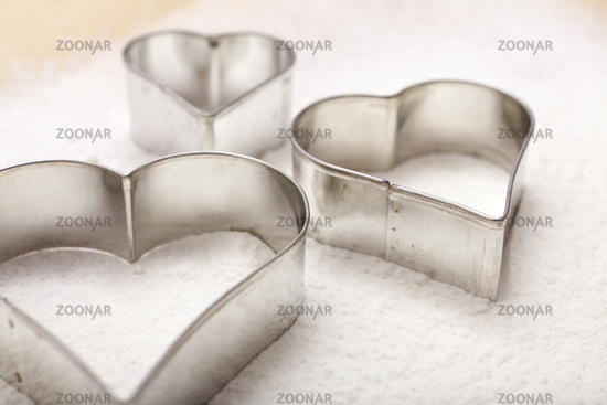 Closeup cookie cutters in flour
