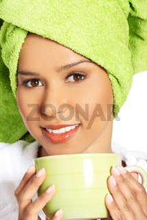 Attractive woman wrapped in towel with turban on head, holding a cup.