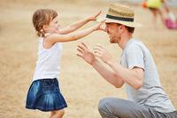 Mädchen spielt mit Vater am Strand