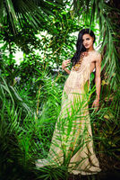 Gorgeous young woman in long evening dress in a forest