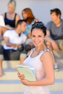 Smiling college student girl hold books summer