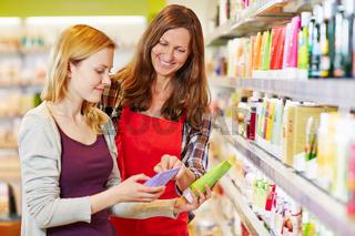 Frau neben Verkäuferin vergleicht Produkte in Drogerie