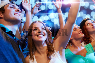 smiling friends at concert in club