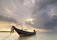Sunset at tropical beach with Thai fishing boat
