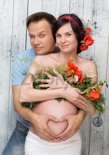 Pregnant woman with husband and flowers