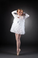 Little ballet dancer posing in white dress