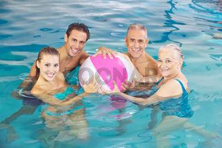Lachende Gruppe mit Wasserball im Schwimmbad