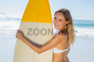 Smiling blonde surfer in white bikini holding her board on the beach