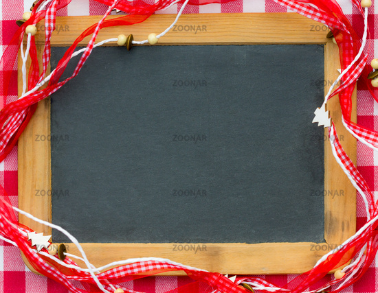 Blackboard blank framed in red Christmas decorations