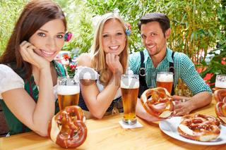 Freunde mit Bier und Brezel im Biergarten