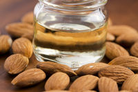 Almond oil with nuts on wooden background