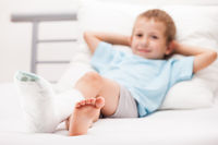 Little child boy with plaster bandage on leg heel