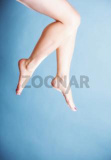 Beautiful long naked woman girl legs on blue