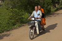 Buddhist monk riding as passenger on a motor-bike