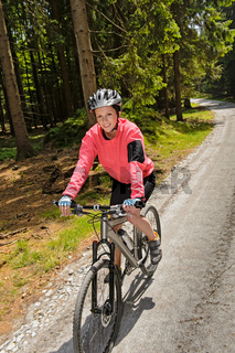 Woman mountain biking in sunny forest smiling