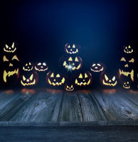 Halloween pumpkins in a dark background and wood f