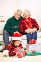 Großeltern betrachten Enkel beim Öffnen von Geschenken