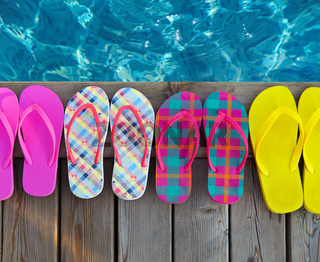 Brightly colored flip-flops on wooden background