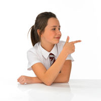 Young schoolgirl pointing to the right of the frame