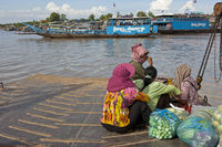 Women crossing the Mekong river on a ferry boat
