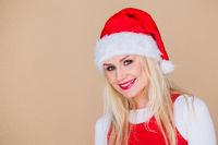 Cheerful blond woman wearing Santa hat