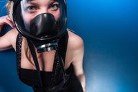 Woman in gasmask against dark background