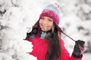winter girl behind snow tree