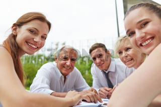 Lachende Geschäftsleute bei Besprechung am Tisch