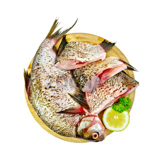 Bream raw on a round board with lemon and parsley