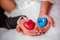 Hands of bride and groom holding stones with love and happiness words