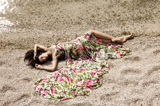 girl lying on the sand by the sea