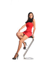 Confident woman sitting on stool and looking at camera