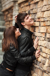 Happy young couple in leather jackets at the brick wall