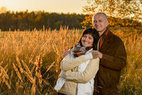 Romantic couple hugging in countryside autumn sunset