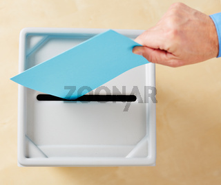 Hand wirft Stimmzettel in Wahlurne