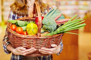 Hände tragen Einkaufskorb voller Gemüse