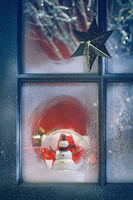 Frosted window with Christmas decoration inside at