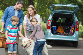 Family with kids and pet dog at picnic