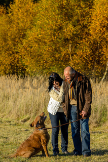 Couple training dog autumn sunset park