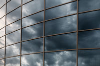 Glass skyscraper wall with reflection of dark stormy clouds at sunset