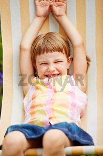 Mädchen liegt im Sommer im Liegestuhl