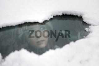 Junge Frau schaut einem verschneiten Auto