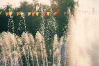 Vintage holidays shot. Jets of a city park fountain and colorful flags.