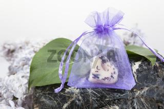 Bodybutter in einem Chiffonsaeckchen auf einem Stein arrangiert