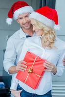 Happy couple celebrating Christmas in Santa hats