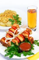 table with food of meat on skewer, dumplings and gass of juice.