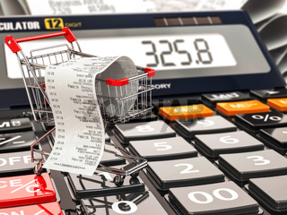Shopping cart on calculator and receipt. Home budget or consumerism concept.
