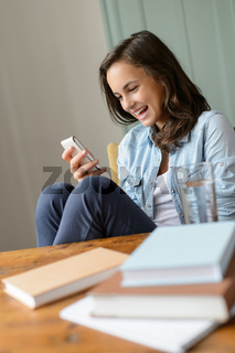 Cheerful teenage girl looking mobile phone home